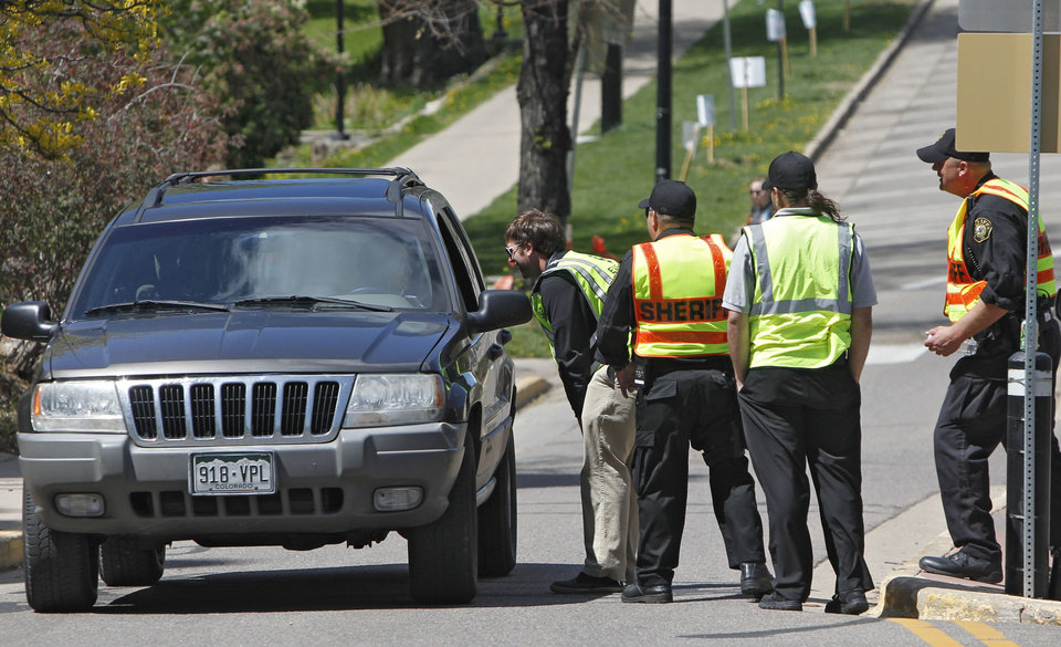 Photo -   Boulder County Sheriff's deputies and University Police check occupants of a vehicle for student ID at the University of Colorado in Boulder, Colo., on Friday, April 20, 2012. The university closed the campus to prohibit an annual 420 marijuana smoke out. (AP Photo/Ed Andrieski)
