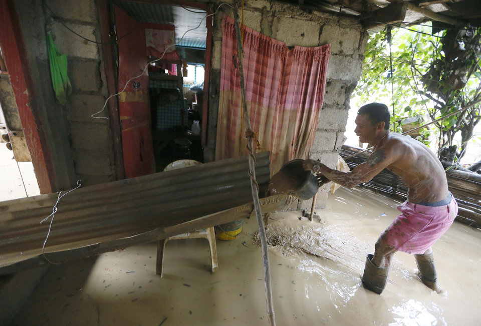 Photo - Gary Suniega removes mud and water which flooded his home at the onslaught of Typhoon Koppu in Cabanatuan city in northern Philippines Tuesday, Oct. 20, 2015. Two days after the typhoon battered northern Philippines and flooded the city and nearby provinces, residents begin the massive clean up of their muddied homes. (AP Photo/Bullit Marquez)