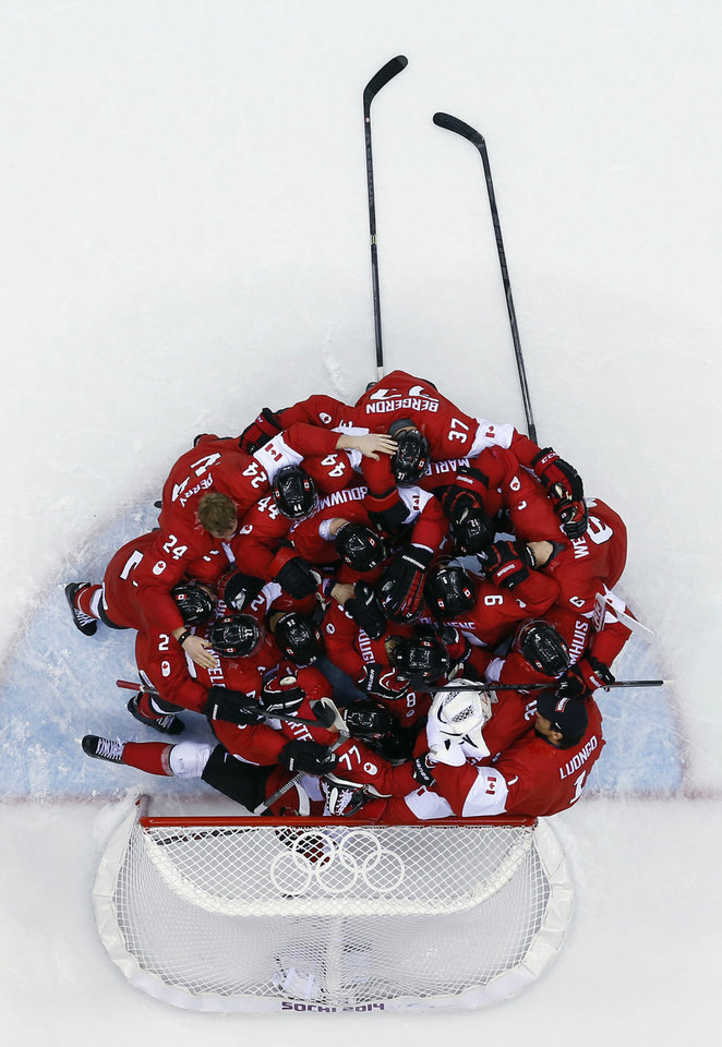 Photo - Canada goaltender Carey Price is swarmed by teammates as they celebrate after the men's gold medal ice hockey game against Sweden at the 2014 Winter Olympics, Sunday, Feb. 23, 2014, in Sochi, Russia. Canada won 3-0 to win the gold medal. (AP Photo/David J. Phillip )
