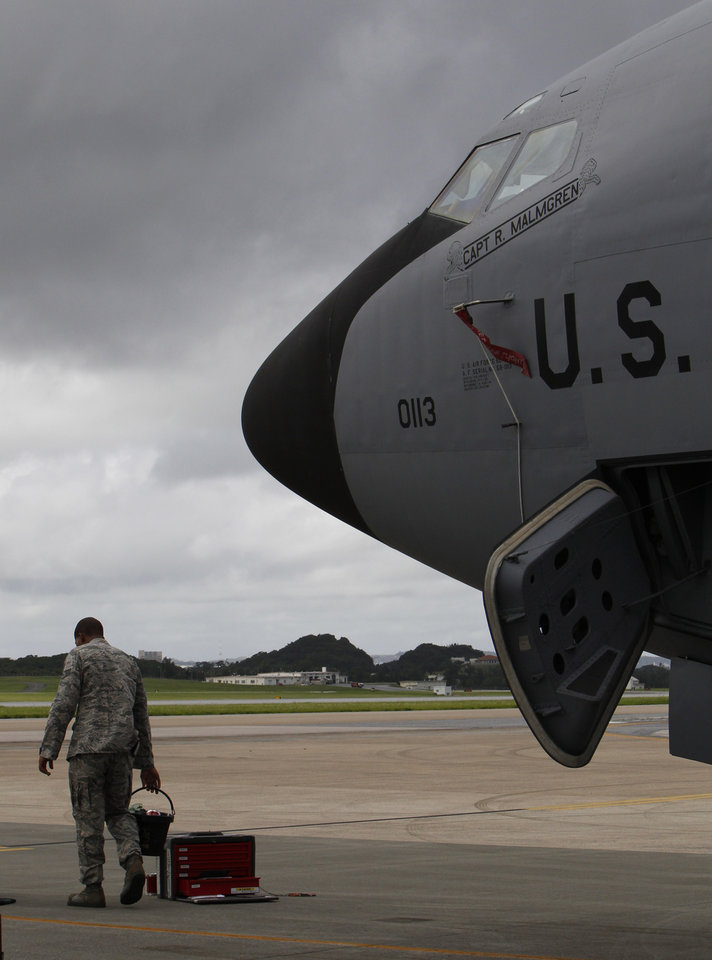 Photo -   In this Aug. 14, 2012 photo, a ground crew member stands in front of a U.S. Air Force KC-135 Stratotanker, which was built in 1958, at Kadena Air Base on Japan's southwestern island of Okinawa. For decades, the U.S. Air Force has grown accustomed to such superlatives as unrivaled and unbeatable. Now some of its key aircraft are being described with terms like decrepit. (AP Photo/Greg Baker)