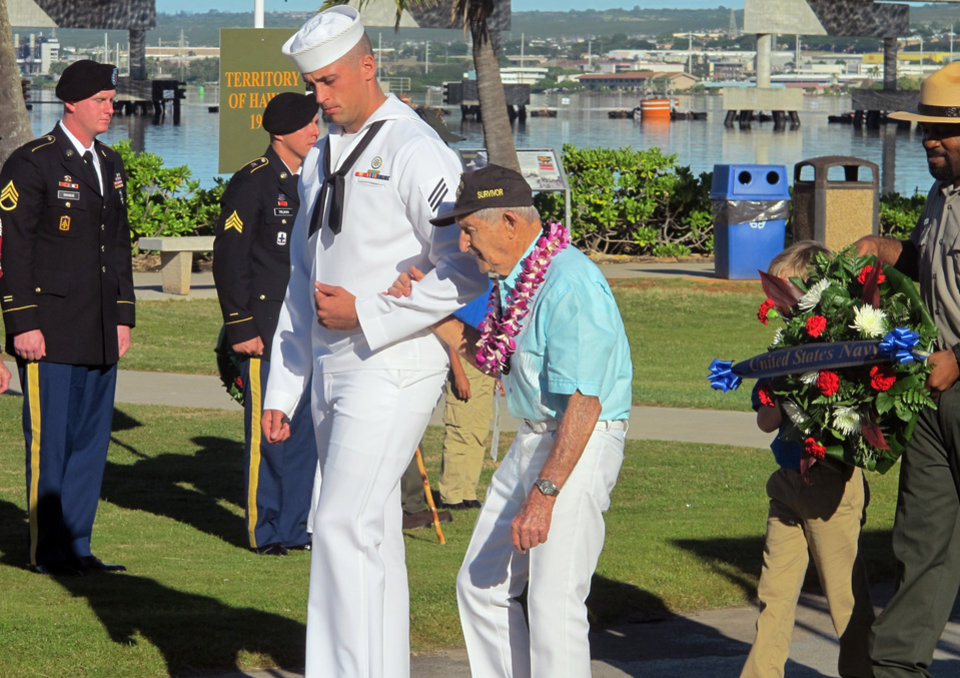 Photo - A Navy sailor escorts Navy veteran and Pearl Harbor survivor John Chapman during a ceremony to mark the 73rd anniversary of the Japanese attack on Pearl Harbor, Sunday, Dec. 7, 2014, at Pearl Harbor, Hawaii. The attack launched the U.S. into World War II. (AP Photo/Jennifer Sinco Kelleher)