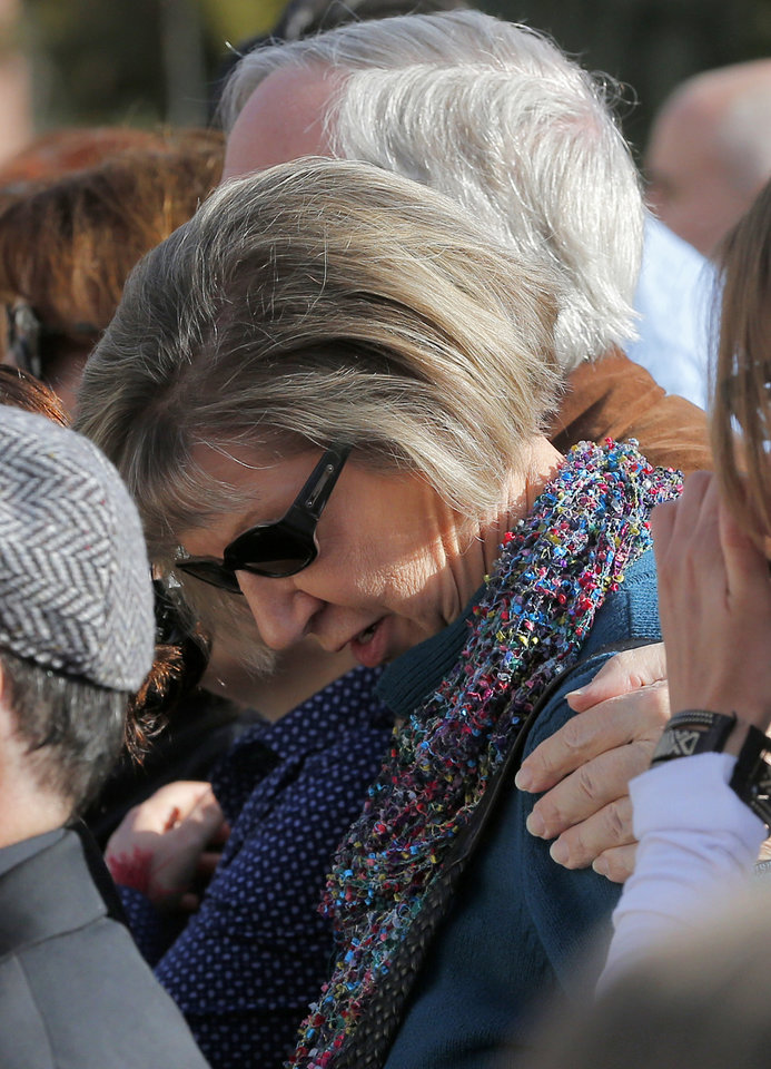 Photo - Tucson shooting survivor Pam Simon lowers her head during a remembrance ceremony on the third anniversary of the Tucson shootings, Wednesday, Jan. 8, 2014, in Tucson, Ariz. Six people were killed and 13 wounded, including U.S. Rep. Gabrielle Giffords, D-Ariz., in the shooting rampage at a community event hosted by Giffords in 2011. Jared Lee Loughner was sentenced in November 2012 to seven consecutive life sentences, plus 140 years, after he pleaded guilty to 19 federal charges in the shooting. (AP Photo/Matt York)