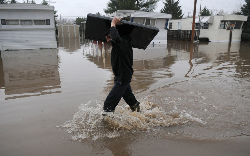Photo - Tim Fitzwater, of Geneseo Ill., carries a flat-screen television out of his father's mobile home in Geneseo on Thursday, April 18, 2013, after the Geneseo Creek pushed out of its banks by heavy rain, flooded the park and threatened several businesses. (AP Photo/The Dispatch, Todd Mizener)  QUAD-CITY TIMES OUT, MANDATORY CREDIT