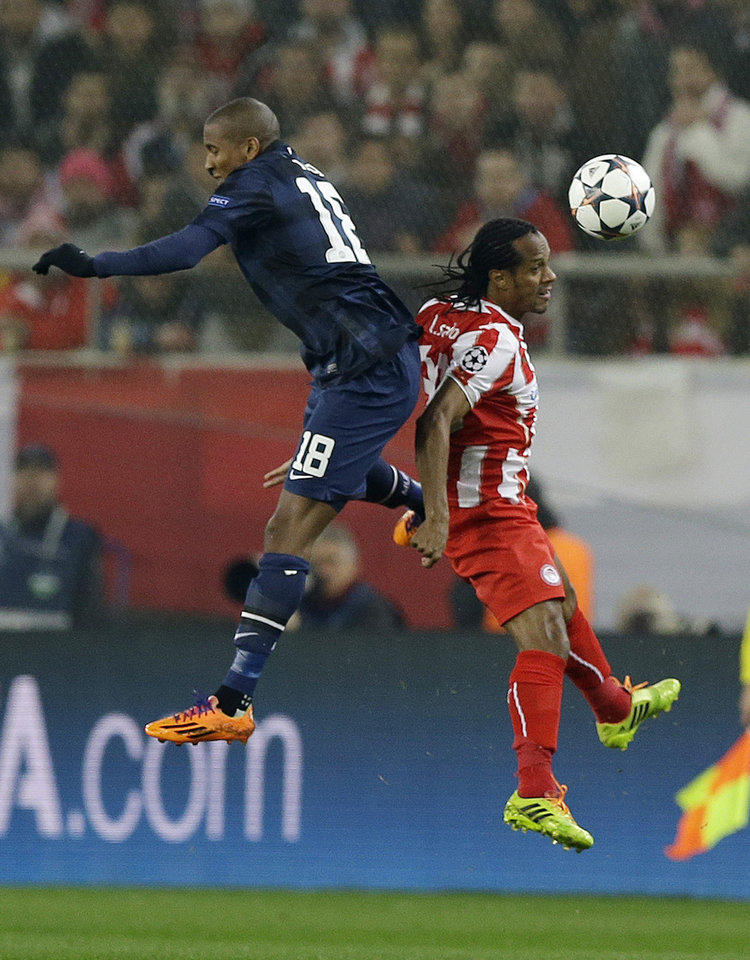 Photo - Olympiakos' Leandro Salino, right, jumps for the ball with Manchester United's Ashley Young during their Champions League, round of 16, first leg soccer match at Georgios Karaiskakis stadium, in Piraeus port, near Athens, on Tuesday, Feb. 25, 2014. (AP Photo/Thanassis Stavrakis)