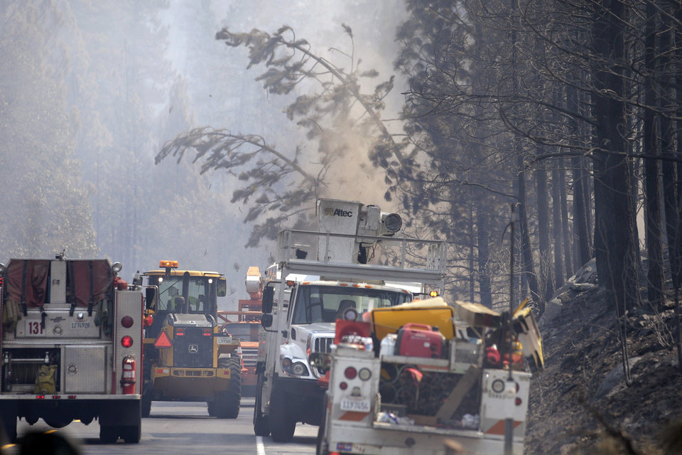Workers cut trees burn by the Rim Fire along Highway 120 near Yosemite National Park, Calif., on Wednesday, Aug. 28, 2013. The giant wildfire burning at the edge of Yosemite National Park is 23 percent contained, U.S. fire officials said Wednesday. (AP Photo/Jae C. Hong)