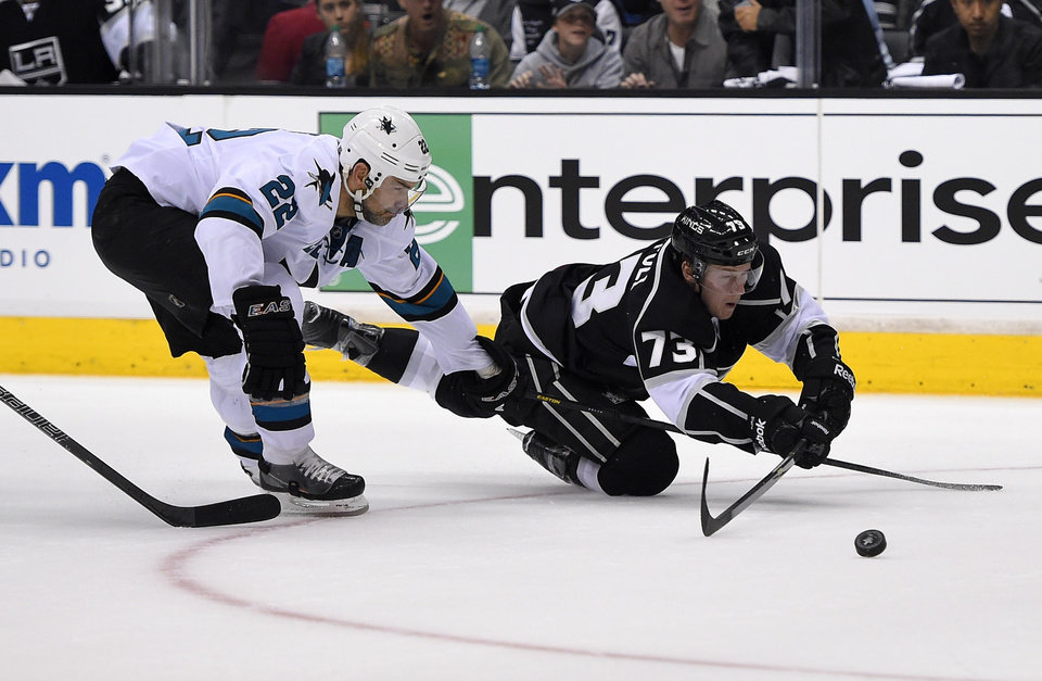 Photo - Los Angeles Kings center Tyler Toffoli, right, trips as he shoots the puck under pressure from San Jose Sharks defenseman Dan Boyle during the second period in Game 3 of an NHL hockey first-round playoff series , Tuesday, April 22, 2014, in Los Angeles. (AP Photo/Mark J. Terrill)