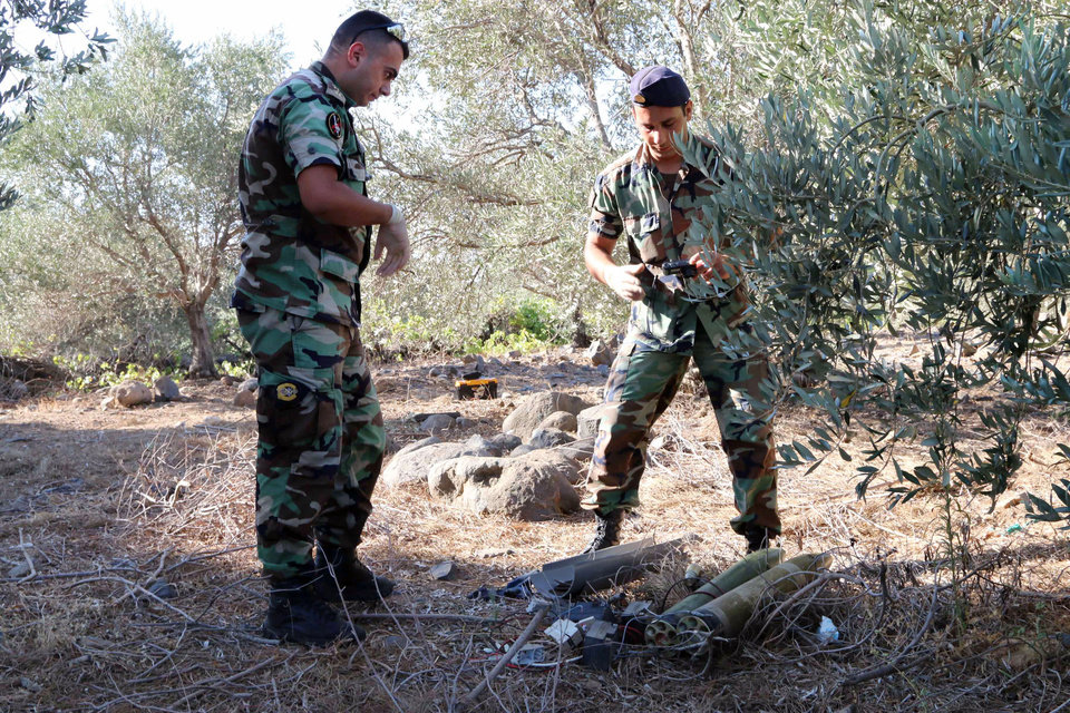 Photo - Lebanese army experts dismantle two rockets that were found ready to fire into northern Israel, in the southern Lebanese village of Al-Mari, Lebanon, Friday, July. 11, 2014. The Lebanese army said in a statement that an