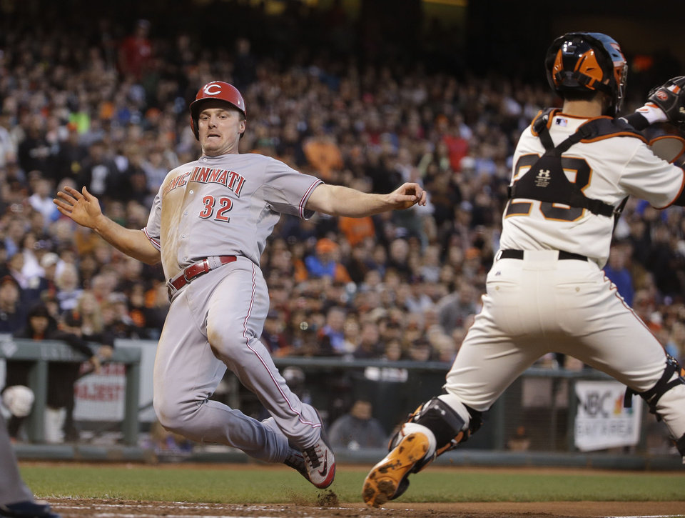 Photo - Cincinnati Reds' Jay Bruce, left, begins his slide into home plate to score the Reds' first run as San Francisco Giants catcher Buster Posey, right, waits for the throw in the fifth inning of their baseball game Thursday, June 26, 2014, in San Francisco. Bruce scored from first after Zack Cozart double to left field. (AP Photo/Eric Risberg)