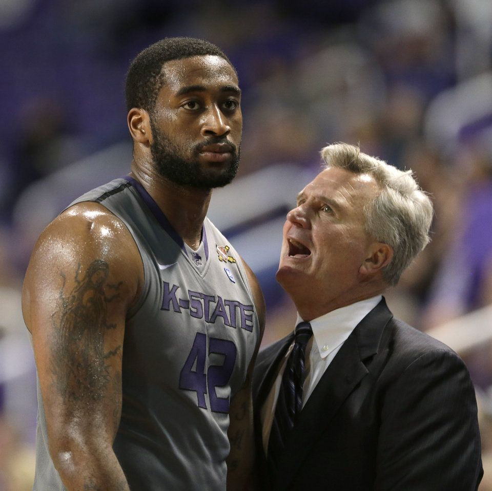 Photo - Kansas State coach Bruce Weber, right, talks to Thomas Gipson during the second half of an NCAA college basketball game against Long Beach State, Sunday, Nov. 17, 2013, in Manhattan, Kan. Kansas State won the game 71-58. (AP Photo/Charlie Riedel)