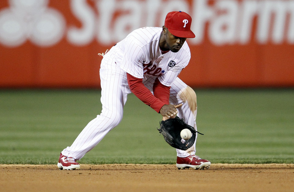 Photo - Philadelphia Phillies' Jimmy Rollins fields a ball hit by Miami Marlins' Marcell Ozuna during the third inning of a baseball game on Friday, April 11, 2014, in Philadelphia. (AP Photo/Tom Mihalek)
