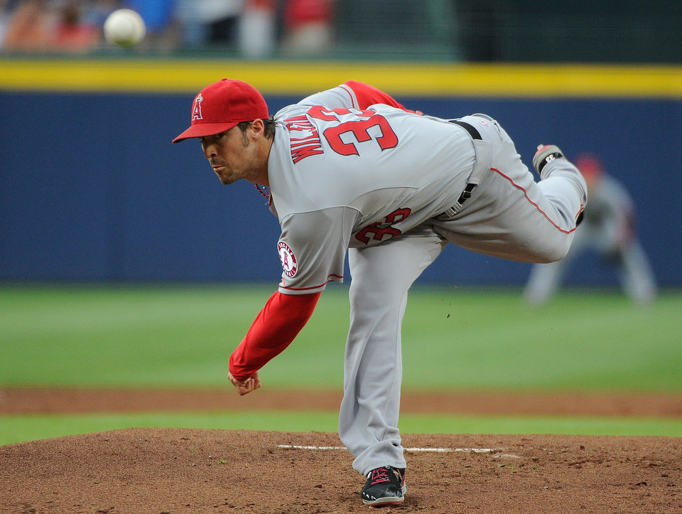 Photo - Los Angeles Angels starting pitcher C.J. Wilson delivers to the Atlanta Braves during the first inning of a baseball game on Friday, June 13, 2014, in Atlanta. (AP Photo/David Tulis)