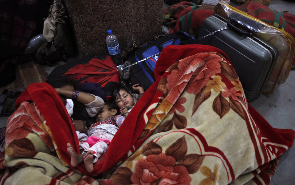 A family sleeps under a blanket on a platform as they wait for the arrival of a train at a railway station in Allahabad, India, Saturday, Dec. 29, 2012. North India continues to face extreme weather conditions with dense fog affecting flights and trains, according to local reports. (AP Photo/Rajesh Kumar Singh)