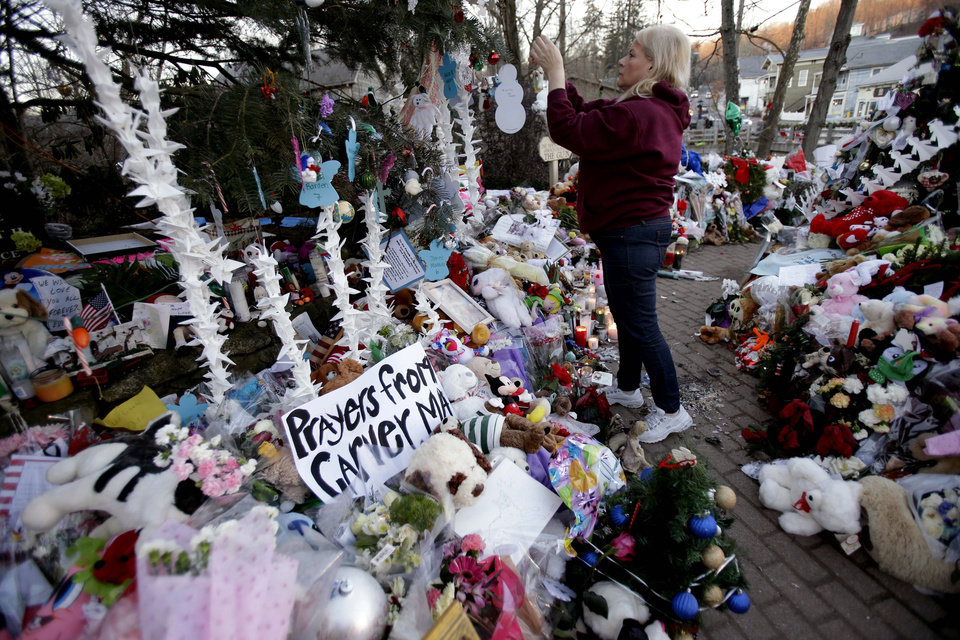 Photo - Nancy Hotchkiss of Naugatuck, Conn. hangs an ornament on a tree at a memorial for the shooting victims in the Sandy Hook village of Newtown, Conn., Thursday, Dec. 20, 2012.  Adam Lanza walked into Sandy Hook Elementary School in Newtown,  Dec. 14, and opened fire, killing 26 people, including 20 children, before killing himself. (AP Photo/Seth Wenig)