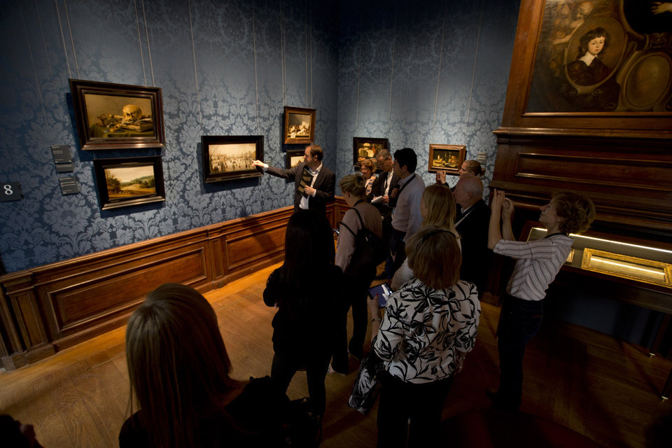 Photo - Visitors listen to a guide during a preview for the press in The Hague, Netherlands, Friday, June 20, 2014. The Mauritshuis reopens after a two-year renovation that allowed its masterpieces, including Vermeer's The Girl with the Pearl Earring to be seen by record-setting crowds abroad. The public will have access for free from 8 pm till midnight on Friday June 27th after the official ceremonial opening and from June 28 onwards the museum will revert to regular opening hours. (AP Photo/Peter Dejong)
