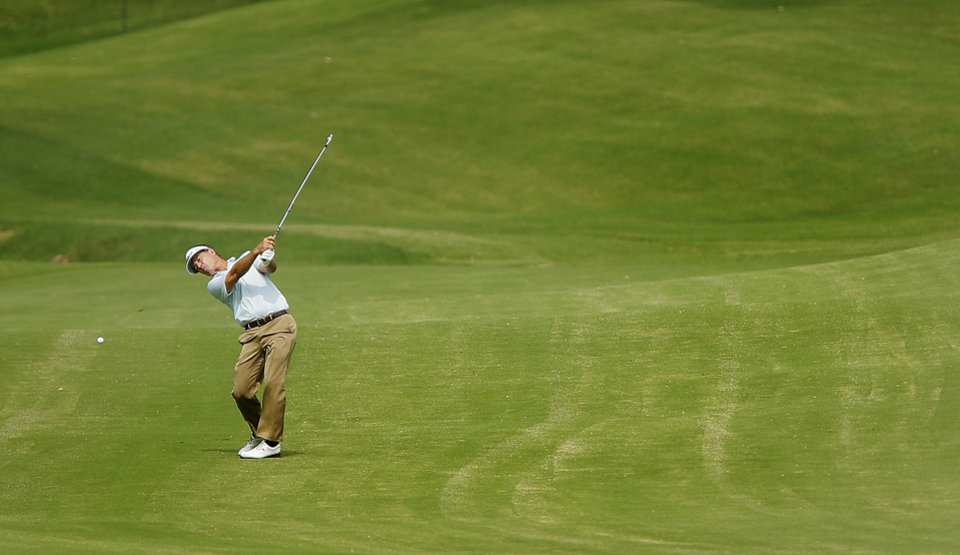 Photo - Dick Mast hits an approach shot on the seventh hole during the first round of the U.S. Senior Open Championship golf tournament at Oak Tree National in Edmond, Okla. on Thursday, July 10, 2014. Photo by Chris Landsberger, The Oklahoman