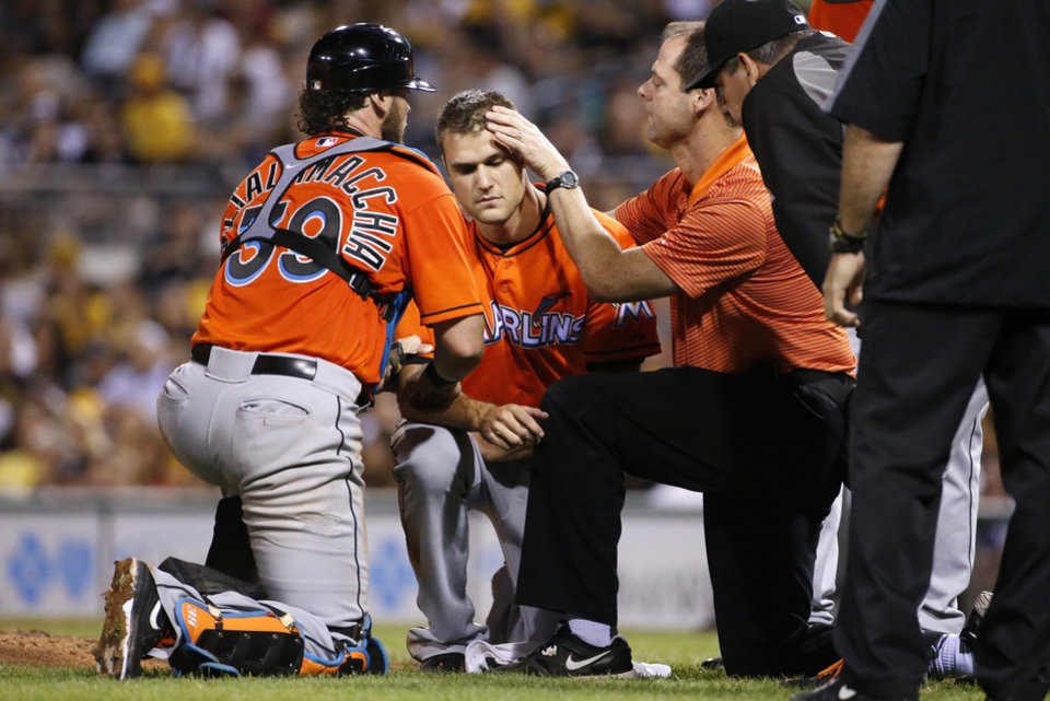Photo - Miami Marlins relief pitcher Dan Jennings, center, is examined by a team trainer as he waits to be driven off the field after being hit by a line drive off the bat of Pittsburgh Pirates' Jordy Mercer during the seventh inning of a baseball game in Pittsburgh Thursday, Aug. 7, 2014.   (AP Photo/Gene J. Puskar)