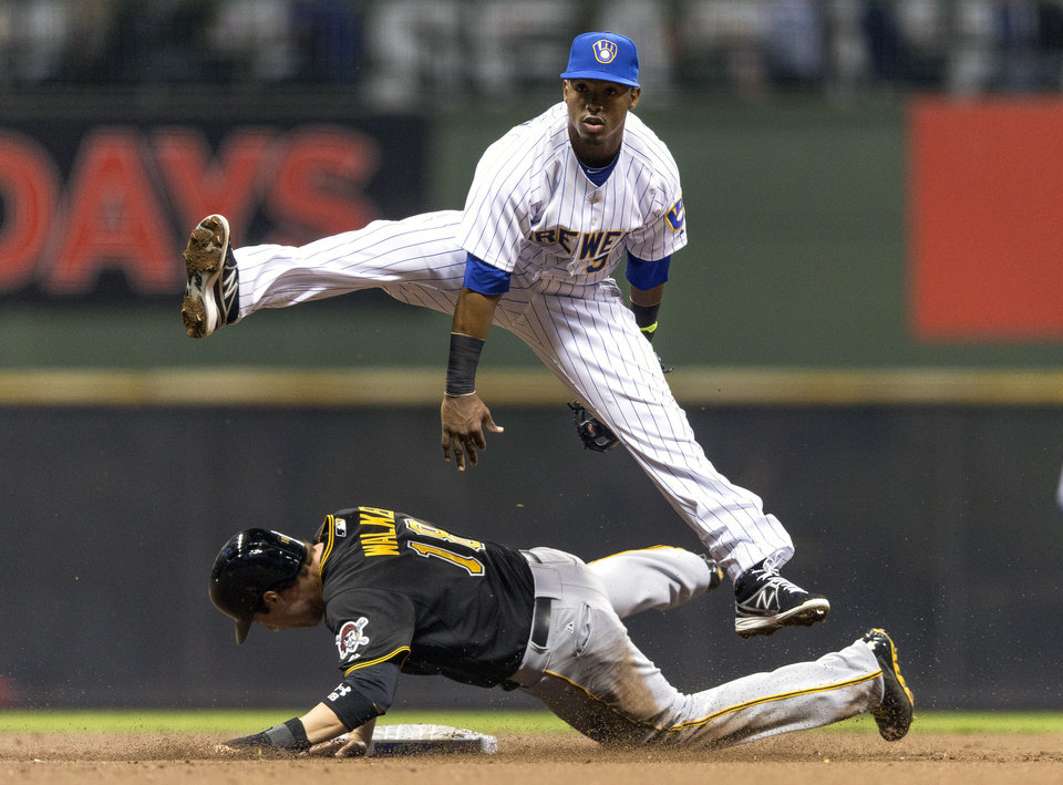 Photo - Milwaukee Brewers' Jean Segura, top, gets the force-out on Pittsburgh Pirates' Neil Walker while turning a double play during the first inning of a baseball game on Friday, April 11, 2014, in Milwaukee. (AP Photo/Tom Lynn)