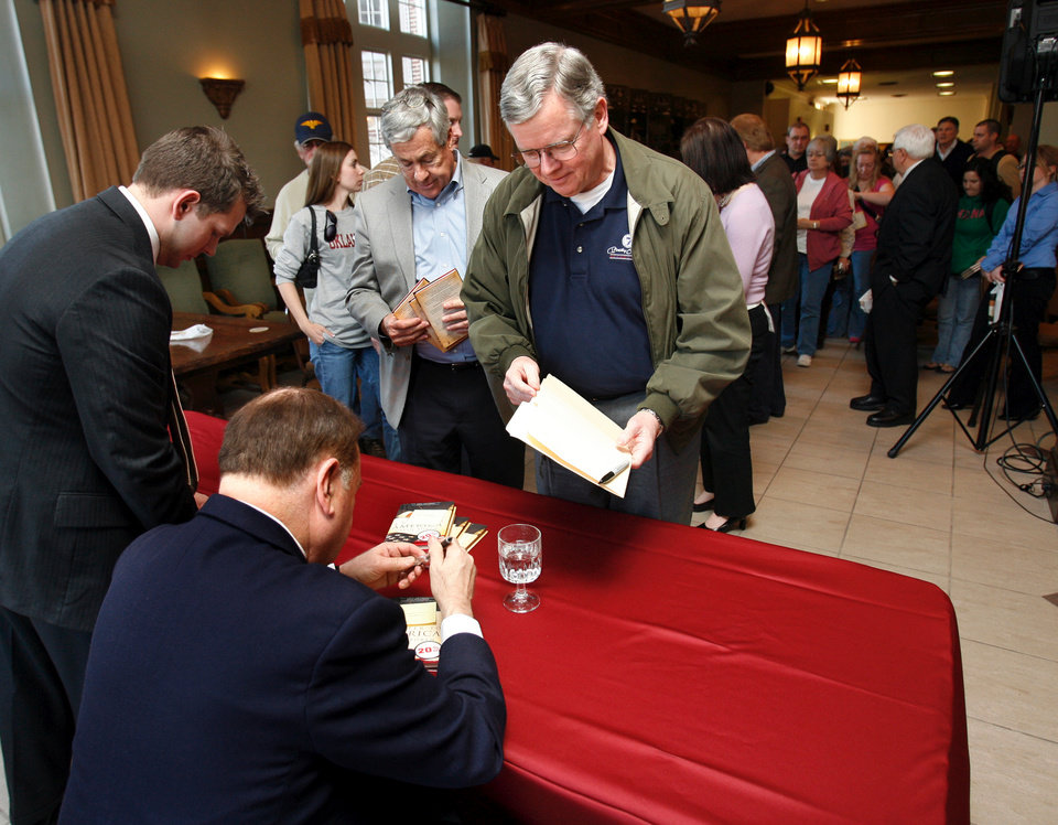 Photo - OU: University of Oklahoma President David Boren signs a stack of books for the first person in line, Carl Johnson of Ada, as he holds a book signing for
