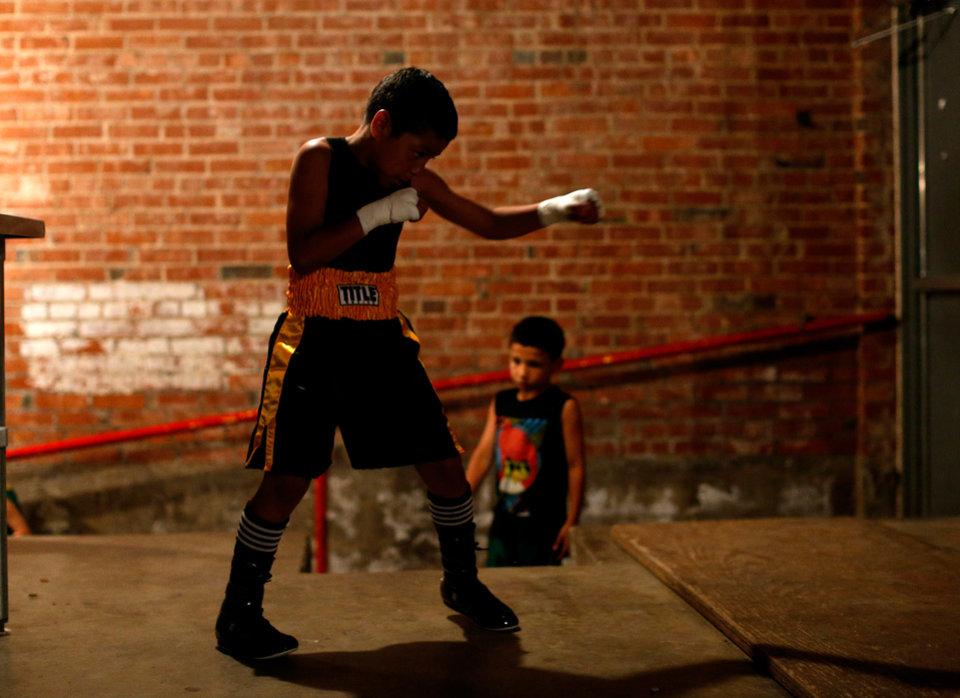 Photo -  Chris Barba, 9, of Edmond, warms up before his first fight at The Underground Arena in Oklahoma City, Saturday, June 15, 2013.