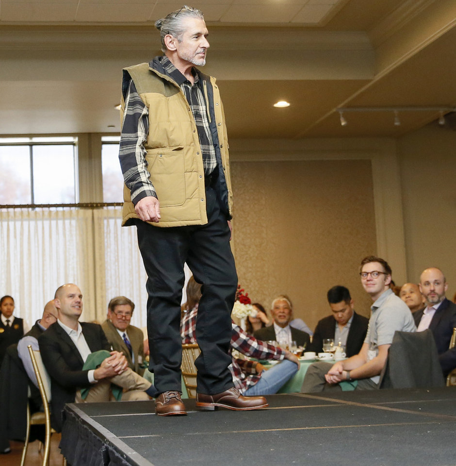 Photo -  Chip Grimmett models clothing from a local boutique as he walks on the runway at the