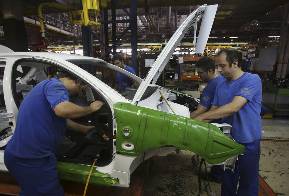 Photo - Iranian car workers assemble a car at the state-run Iran-Khodro automobile manufacturing plant near Tehran, Iran, Sunday, June 29, 2014. Iran began exporting automobiles to Russia for the first time in five years on Sunday, after meeting upgraded emission standards, the country's largest auto manufacturer said. (AP Photo/Vahid Salemi)