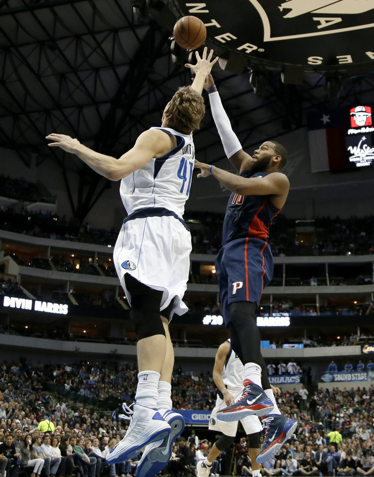 Photo - Dallas Mavericks power forward Dirk Nowitzki (41), of Germany, defends against a shot attempt by Detroit Pistons' Greg Monroe (10) in the first half of an NBA basketball game, Sunday, Jan. 26, 2014, in Dallas. (AP Photo/Tony Gutierrez)