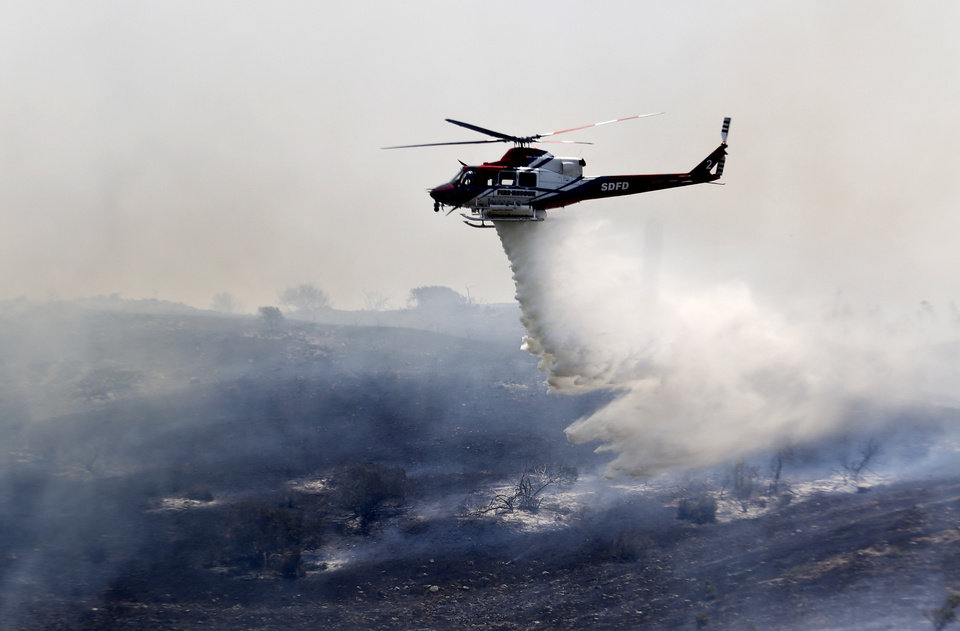 Photo - A helicopter attacks a wildfire burning in the north county of San Diego Tuesday, May 13, 2014, in San Diego. Wildfires pushed by gusty winds chewed through canyons parched by California's drought, prompting evacuation orders for more than 20,000 homes on the outskirts of San Diego and another 1,200 homes and businesses in Santa Barbara County 250 miles to the north. (AP Photo)