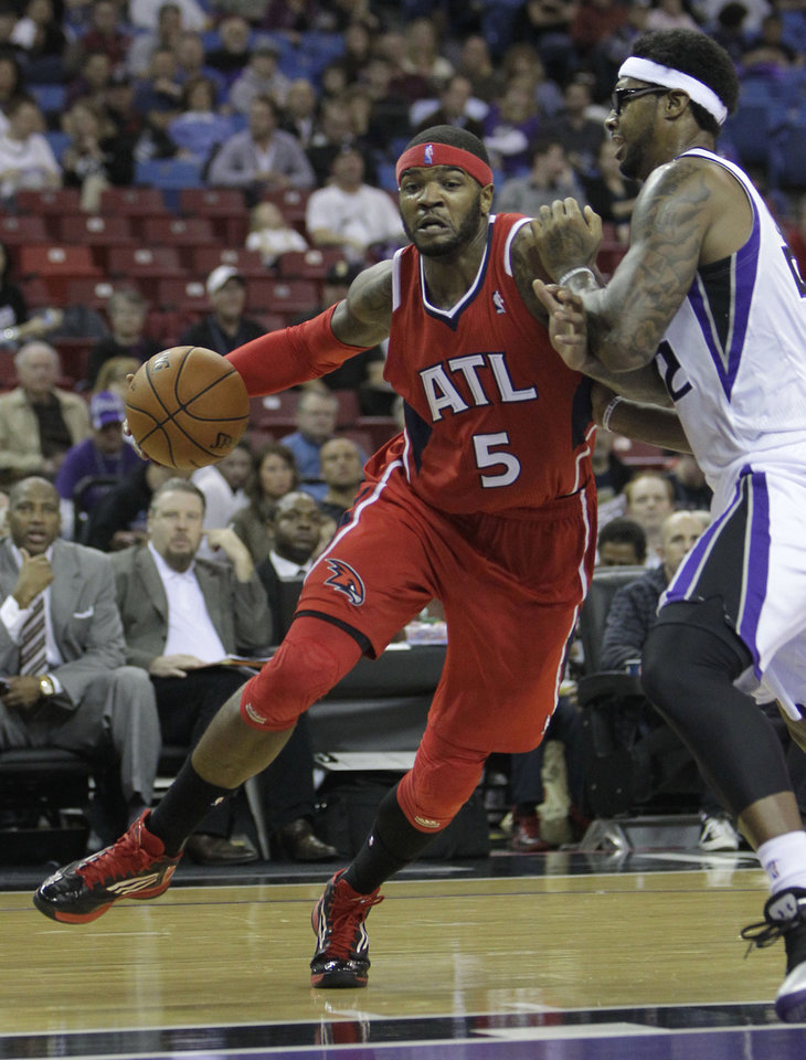 Atlanta Hawks forward Josh Smith, left, drives to the basket against Sacramento Kings forward James Johnson during the first half of an NBA basketball game in Sacramento, Calif., Friday, Nov. 16, 2012. (AP Photo/Rich Pedroncelli)