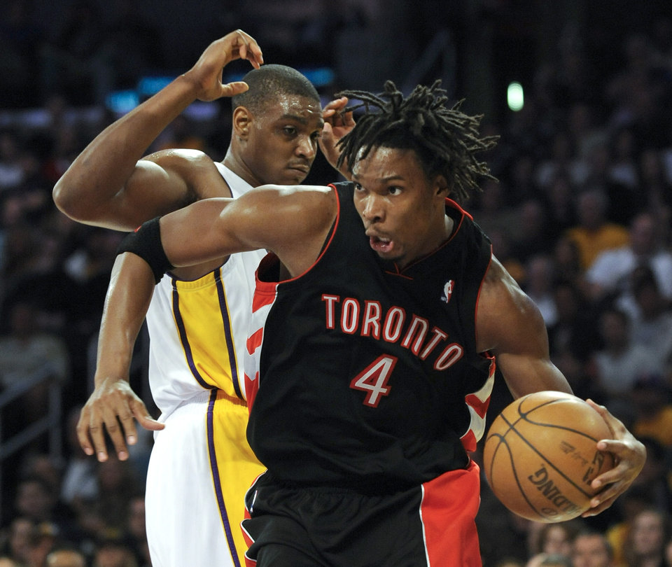 Photo - Toronto Raptors forward Chris Bosh (4) gets by Los Angeles Lakers center Andrew Bynum, left, in the first half of their NBA basketball game, Sunday, Nov. 30, 2008 in Los Angeles. (AP Photo/Gus Ruelas) ORG XMIT: LAS104