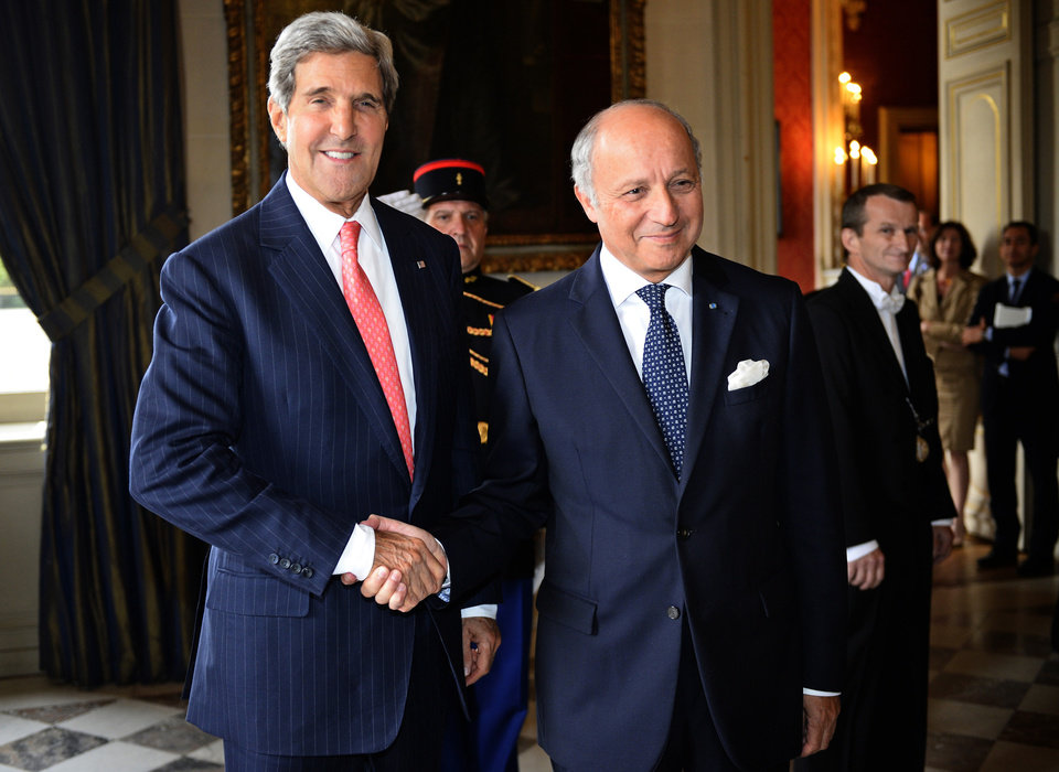 Photo - French Foreign Affairs Minister Laurent Fabius, center  shakes hands with US Secretary of State John Kerry at the ministry in Paris, on Saturday Sept.7, 2013. Kerry traveled to Europe to court international support for a possible strike on the Syrian regime for its alleged use of chemical weapons while making calls back home to lobby Congress where the action faces an uphill battle.(AP Photo/Lionel Bonaventure/Pool)