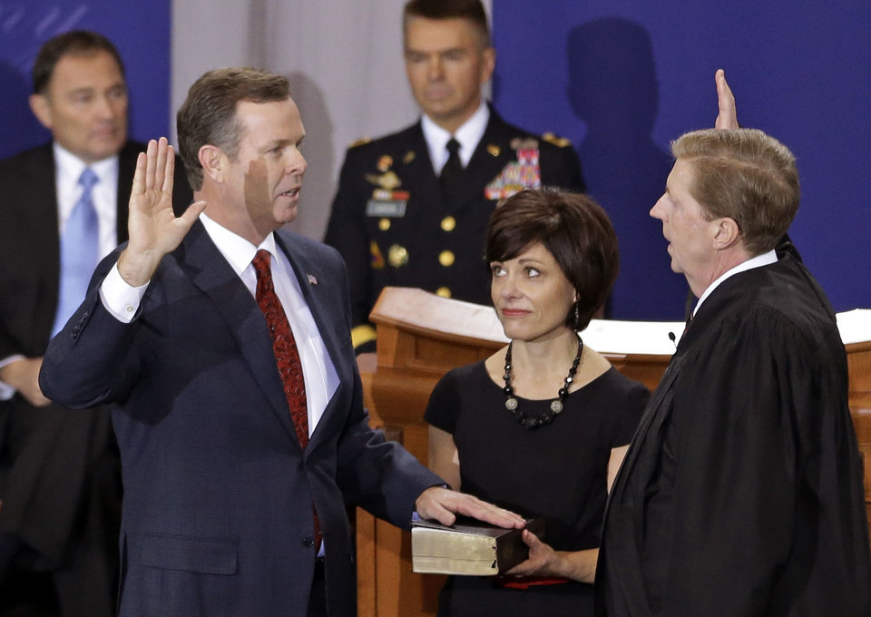 Photo - FILE -  In this Jan. 7, 2013 file photo, Utah Attorney General John Swallow, left, is sworn in by Chief Justice Matthew B. Durrant, right, at the Utah Sate Capitol Rotunda, in Salt Lake City. Swallow announced during an news conference that he is stepping down amid multiple investigations of bribery and misconduct that have hounded him ever since he took office at the beginning of the year. (AP Photo/Rick Bowmer, File)
