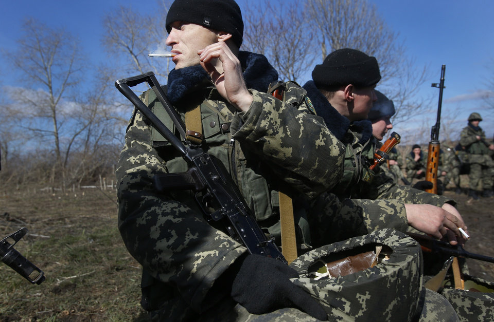 Photo - Ukrainian border guards take a break during training at a military camp in the village of Alekseyevka on the Ukrainian-Russian border, eastern Ukraine, Friday, March 21, 2014. Russian President Vladimir Putin signed bills on Friday making Crimea part of Russia, completing the annexation from Ukraine. (AP Photo/Sergei Grits)