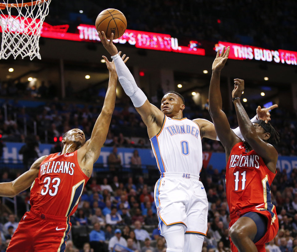 Photo - Oklahoma City's Russell Westbrook (0) tries to score between New Orleans' Wesley Johnson (33) and Jrue Holiday (11) during an NBA basketball game between the Oklahoma City Thunder and the New Orleans Pelicans at Chesapeake Energy Arena in Oklahoma City, Monday, Nov. 5, 2018. Photo by Nate Billings, The Oklahoman