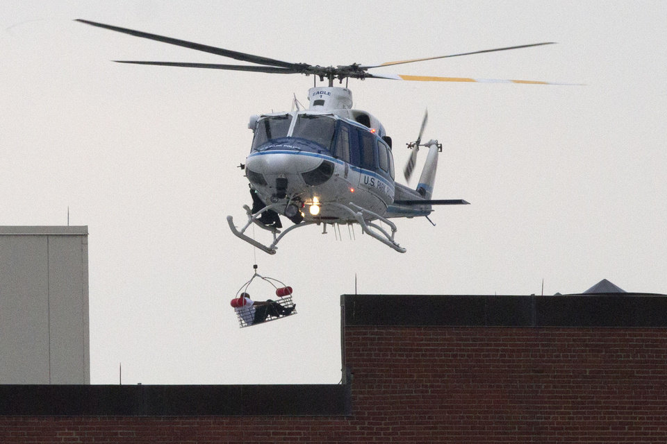 Photo - A U.S. Park Police helicopter removes a man in a basket from the Washington Navy Yard Monday, Sept. 16, 2013.    Earlier in the day, the U.S. Navy said it was searching for an active shooter at the Naval Sea Systems Command headquarters, where about 3,000 people work.  The exact number of people killed and the conditions of those wounded was not immediately known.  (AP Photo/Jacquelyn Martin)