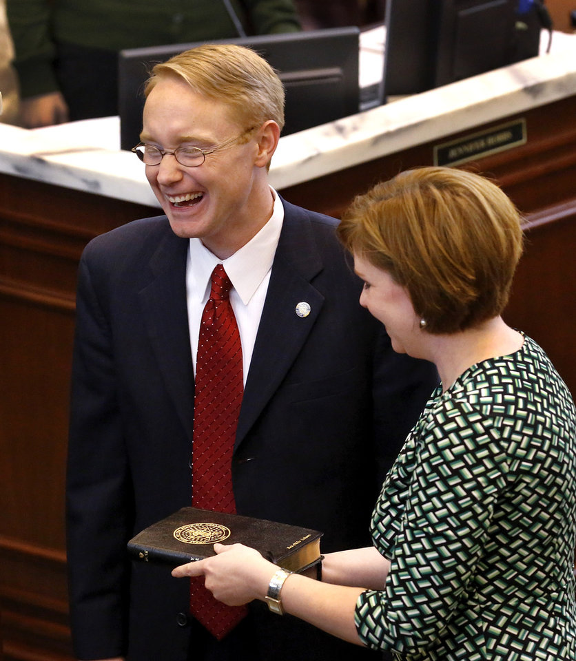 Rep. Mike Jackson laughs as he and his wife switched positions twice before settling on him standing on her right as he is worn in as the speaker pro tempore in the House of Representatives. T. W. Shannon was elected by his colleagues in the Oklahoma House of Representatives as their Speaker for the upcoming legislative session. Shannon, a Democrat from Lawton, is Oklahoma's first black Speaker of the House. He was sworn in on the floor of the House by Oklahoma Supreme Court Chief Justice Tom Colbert on Tuesday, Jan. 8, 2013.  Colbert became  Oklahoma's first black chief justice when he was sworn in last week.    Photo by Jim Beckel, The Oklahoman