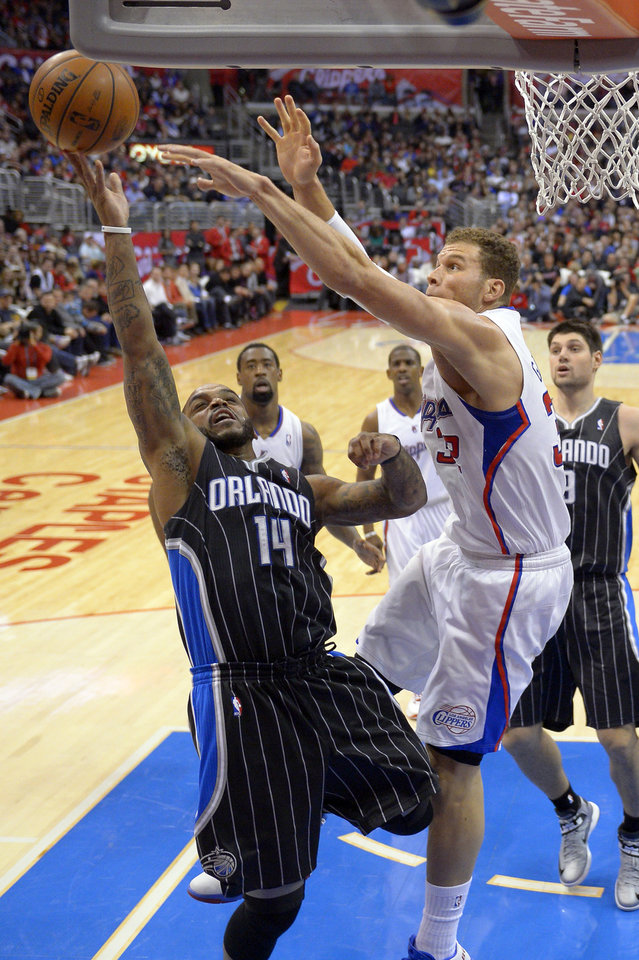 Photo - Orlando Magic guard Jameer Nelson, left, goes up for a shot as Los Angeles Clippers  forward Blake Griffin defends during the first half of their NBA basketball game, Saturday, Jan. 12, 2013, in Los Angeles. (AP Photo/Mark J. Terrill)