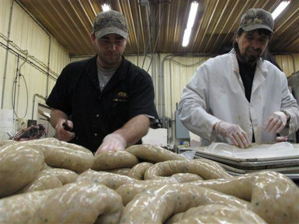 In this Wednesday, April 10, 2013 photo, processing department workers Chris Cote, left, and William Brooks at the Country Store market prepare links of boudin to be sold in the meat counter in Pennsdale, Pa. The sausage is popular in Louisiana. An influx of workers from the South to fill jobs in the natural gas industry in north-central Pennsylvania has led area catering businesses, restaurants and grocery stores to offer more Southern cuisine like jambalaya and boudin. (AP Photo/Genaro C. Armas)