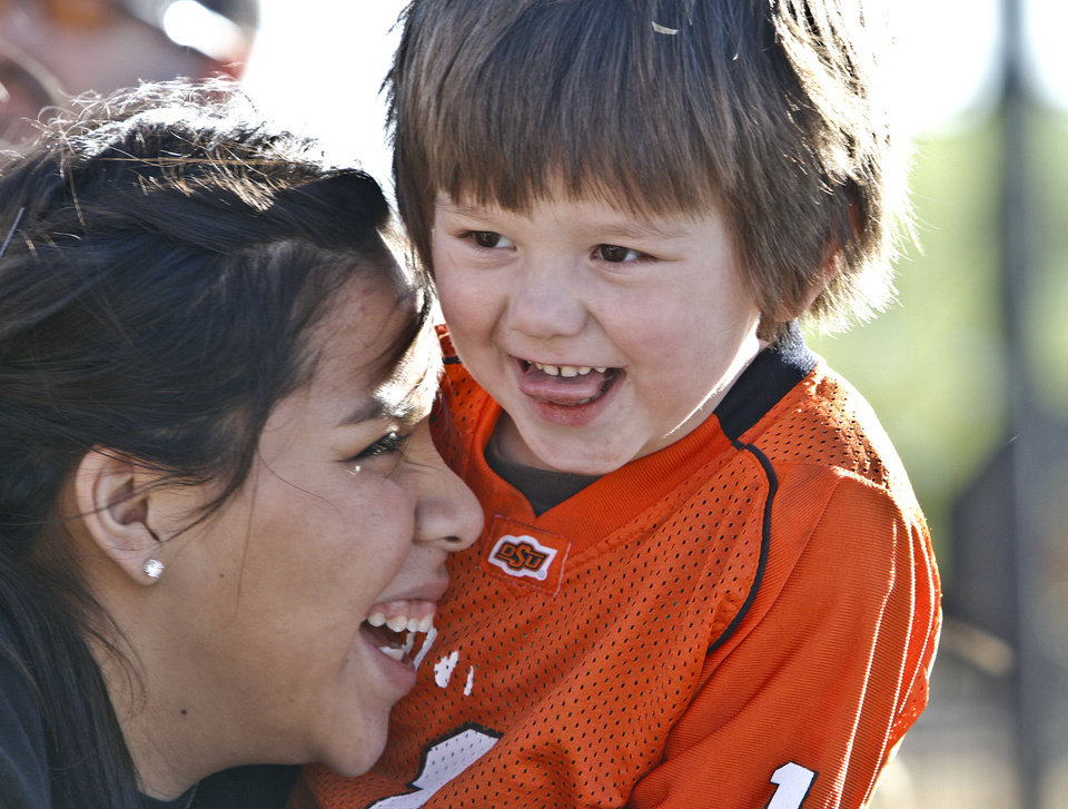 Drew Baker, left, and Lucas Crawford, 4, laugh together while waiting for the Oklahoma State University football team arrives at the Stillwater Airport from their BCS Fiesta Bowl win on Tuesday, Jan. 3, 2012, in Stillwater, Okla. The Cowboys defeated Stanford 41-38 in overtime. Photo by Chris Landsberger, The Oklahoman