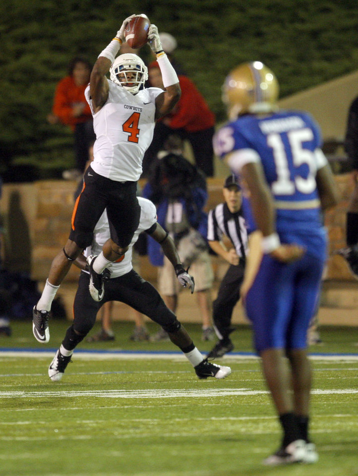 Oklahoma State's Justin Gilbert (4) intercepts a pass as Tulsa's Kalen Henderson (15) looks on during a college football game between the Oklahoma State University Cowboys and the University of Tulsa Golden Hurricane at H.A. Chapman Stadium in Tulsa, Okla., Sunday, Sept. 18, 2011. Photo by Sarah Phipps, The Oklahoman