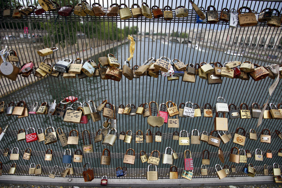 Photo - Love padlocks are seen on the Solferino bridge after a chunk of fencing with thousands of locks fell off under their weight on the Pont des Arts bridge, in Paris, Monday, June 9, 2014. The fencing tumbled late Sunday on the pedestrian bridge, which crosses the Seine. Thousands of couples have latched padlocks to the bridge and thrown their keys into the river as symbols of lasting love, resulting in what some decry as an eyesore. (AP Photo/Francois Mori)