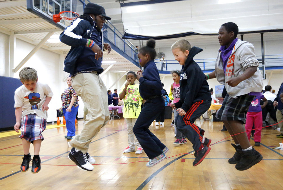 Photo - From left, Lincoln Smith, Benjamin Nsakashalo, Abria Glenn, Mason Euer and Devin Hawthorne jump rope during YMCA Healthy Kids Day at the Northside YMCA. PhotoS by Sarah Phipps, The Oklahoman