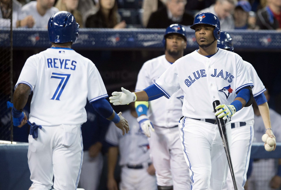 Photo - Toronto Blue Jays' Edwin Encarnacion, right, and Jose Reyes celebrate after Reyes scored in the third inning of a baseball game against the Philadelphia Phillies in Toronto on Thursday, May 8, 2014. (AP Photo/The Canadian Press, Darren Calabrese)