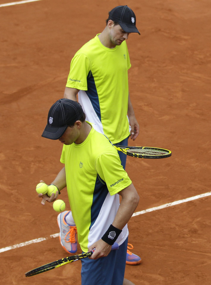Photo - USA's Bob, foreground, and Mike Bryan cross as they play Spain's Marcel Granollers and Marc Lopez during their quarterfinal match of  the French Open tennis tournament at the Roland Garros stadium, in Paris, France, Monday, June 2, 2014. The Spanish pair won 6-4, 6-2. (AP Photo/Darko Vojinovic)