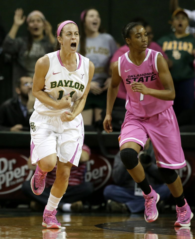 Photo - Baylor's Makenzie Robertson (14) celebrates after scoring a 3-point basket in front of Oklahoma State's Brittany Atkins (1) in the first half of an NCAA college basketball game on Sunday, Feb. 9, 2014, in Waco, Texas. Both teams wore uniforms accented with pink for breast cancer awareness. (AP Photo/Tony Gutierrez)