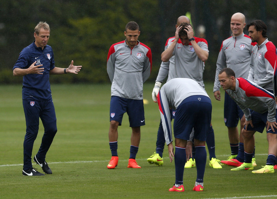 Photo - United States head coach Juergen Klinsmann, left, addresses his team during a training session at the Sao Paulo FC training center in Sao Paulo, Brazil, Tuesday, June 10, 2014. Klinsmann arrived in Brazil on Tuesday, a day after the team's arrival, because he stayed behind in Miami to watch a friendly between Ghana and South Korea. The U.S. will play against Ghana on June 16 in group G of the 2014 soccer World Cup. (AP Photo/Julio Cortez)