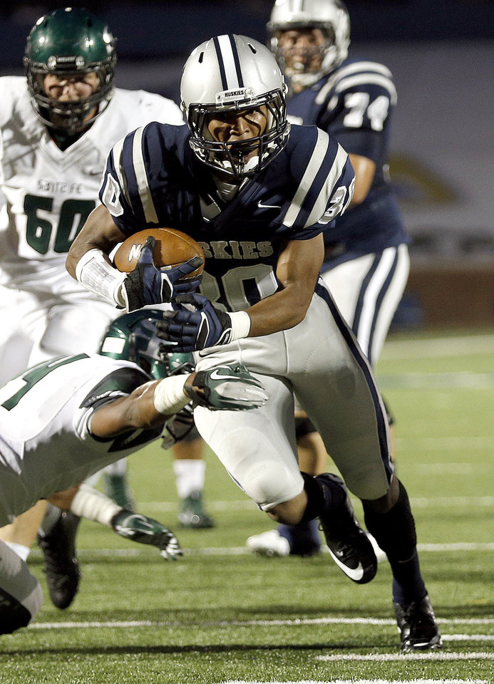 Photo - Edmond North's Richard McCauley tries to get by Edmond Santa Fe's Ke'Marrie Carter-Hartfield during the high school football game between Edmond North High School and Edmond Santa Fe High School at Wantland Stadium in Edmond, Okla.,  Friday, Sept. 20, 2013. Photo by Sarah Phipps, The Oklahoman