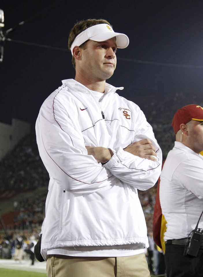 Photo - FILE - In this Nov. 24, 2012 file photo, Southern California head coach Lane Kiffin looks on as senior quarterback Matt Barkley is introduced to the crowd during a ceremony for the seniors before an NCAA college football game against Notre Dame, in Los Angeles. Southern California is coming off a historically disappointing season that has put Kiffin in precarious situation heading into his fourth season as Trojans coach. The Trojans will have a new quarterback and are still dealing with a roster limited by NCAA sanctions. They won't enter the season No. 1 like last year. Expectations are far more modest, which both Kiffin and his boss, athletic director Pat Haden, say is a good thing. (AP Photo/Danny Moloshok, File)