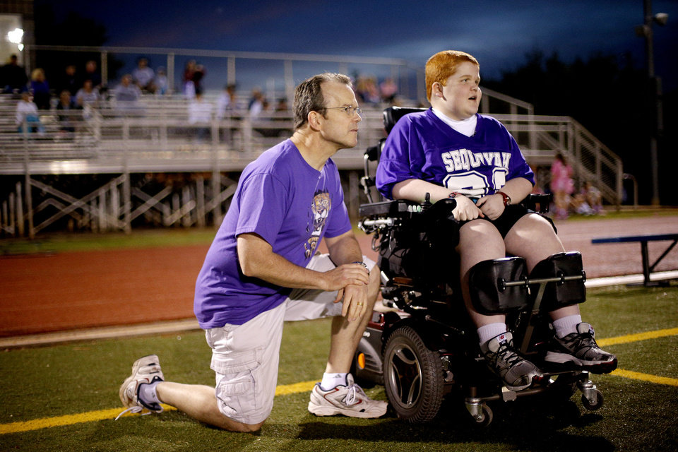Photo - Keegan Erbst talks with his father, Scott, during a Sequoyah Middle School football game, Thursday, September 27, 2012. Keegan, who has muscular dystrophy and is confined to a wheelchair, got involved with the team after players Lucas Coker, Colton James, and Parker Tumleson, pushed suggested it to the coach.  Photo by Bryan Terry, The Oklahoman