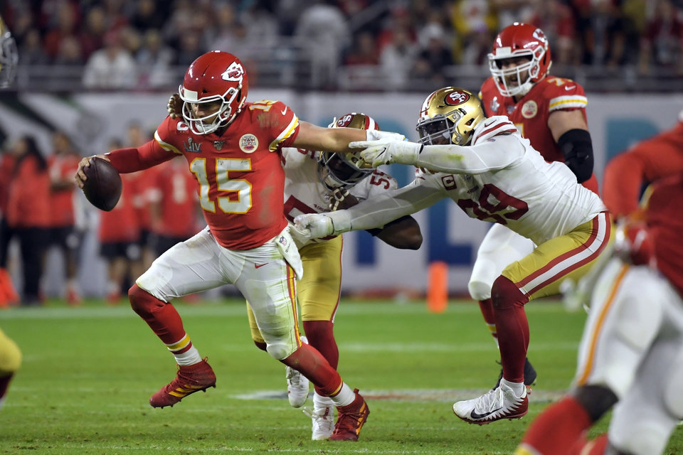 Photo - Kansas City Chiefs' quarterback Patrick Mahomes, left, tries to scramble away from San Francisco 49ers' Dee Ford, center, and DeForest Buckner, right, during the second half of the NFL Super Bowl 54 football game Sunday, Feb. 2, 2020, in Miami Gardens, Fla. (AP Photo/Mark J. Terrill)