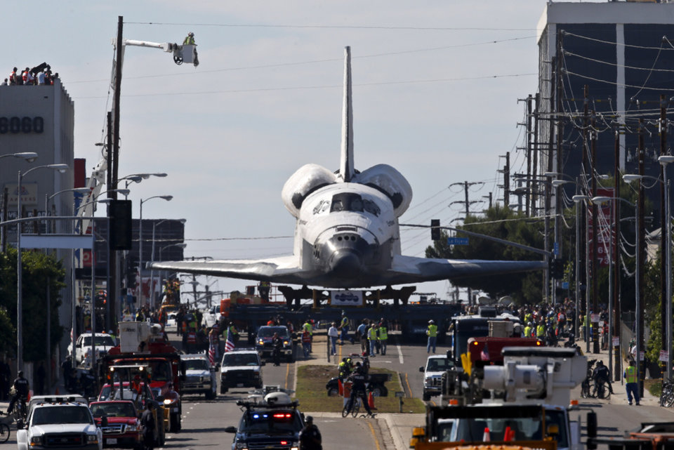 The Space Shuttle Endeavour slowly moves along city streets on a 160-wheeled carrier in Los Angeles, Friday, Oct. 12, 2012. Endeavour's 12-mile road trip kicked off shortly before midnight Thursday as it moved from its Los Angeles International Airport hangar en route to the California Science Center, its ultimate destination. (AP Photo/Jae C. Hong)